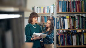 Female University Student Working In Library With Tutor stock footage