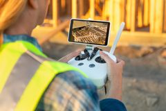 Female Unmanned Aircraft System UAV Quadcopter Drone Pilot. With Controller Inspecting New House Framing stock photo