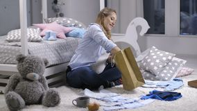 Female unpacking shopping bag with baby clothes. Lovely young adult pregnant female after shopping for newborn baby clothes. Expecting mother sitting in children stock video footage