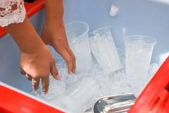 Female use metal ice scoop and plastic cup in ice bucket.  stock photography