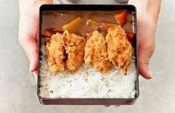 A female uses hands to holding and handing a dish of Japanese curry rice topping with fried chicken and vegetables. royalty free stock photos