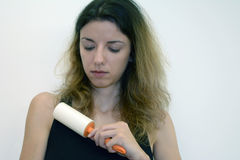 Female uses a roller. Female model uses a hair roller to clean the cat hair off her clothes Royalty Free Stock Photo