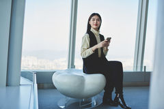 Female is using cell telephone, while is sitting in luxury office interior with modern design Royalty Free Stock Image