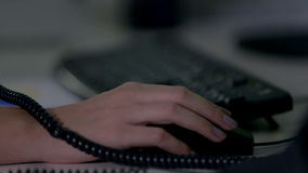 Female using a computer mouse while talking to her customer over the phone stock footage
