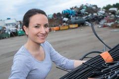 Female using crane with rubbish car scrapyard. Female using a crane with rubbish car scrapyard Stock Photos