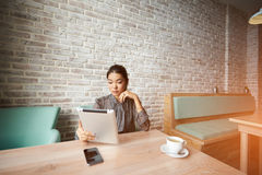 Female using digital tablet for search information for coming meeting. Charming businesswoman reading feminine article in social network via touch pad while Royalty Free Stock Image