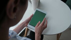 Female using digital tablet. Top view - Female hands using digital tablet with green screen, sitting in cafe stock footage