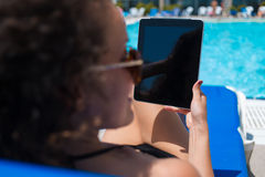 Female using her digital tablet while lying on deck chair near pool in hotel Stock Image