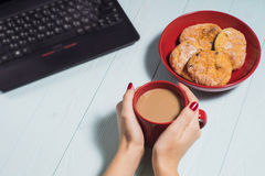 Female using laptop with a coffee cup on wooden table. Stock Photography