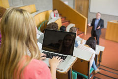Female using laptop with students and teacher at lecture hall. Rear view of a female using laptop with students and teacher at the college lecture hall Stock Image