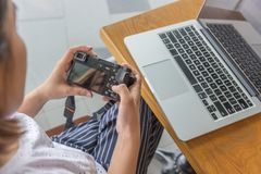 Female using mirrorless camera when preview images. Female using camera when preview images beside laptop royalty free stock photography