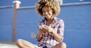 Female Using Mobile Phone On A Road. Young female using mobile phone while sitting on a road slow motion stock footage