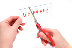 Female using scissors to remove the word unhappy to read happy Royalty Free Stock Photo