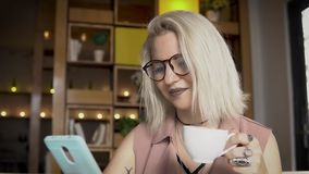 Female using smartphone while drinking coffee. Young female using smartphone while drinking coffee stock video