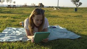 Female using tablet in the park with sea at horizon stock footage
