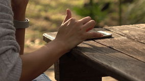 Female using touch screen on smartphone in the park. Female using touch screen on smartphone with wooden desk in the park stock video footage