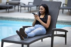 Female on a Vacation using a Voice Assistant on a Smart Phone. Black female on a speaker phone call in a hotel resort.  She is working while on vacation or Stock Image