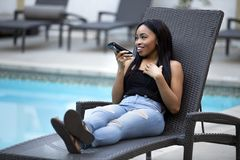 Female on a Vacation using a Voice Assistant on a Smart Phone. Black female on a speaker phone call in a hotel resort.  She is working while on vacation or Royalty Free Stock Photography