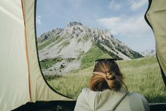 Female vacationer camper in tent Looking At mountain view in Mon Royalty Free Stock Images