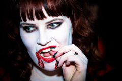 A female vampire. A female vampire checking her teeth royalty free stock photo