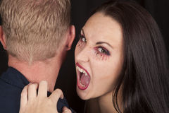 Female vampire bite mans neck fangs. A female vampire getting ready to take a bite out of a man's neck Stock Images
