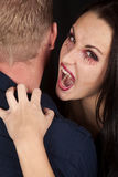 Female vampire bite mans neck look Stock Photography