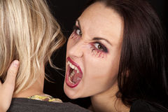 Female vampire bite womans neck looking. A female vampire getting ready to take a bite out of a woman's neck Stock Photos