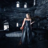 Female vampire with cup of blood in old castle Royalty Free Stock Photo