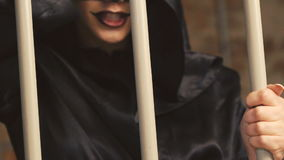Female vampire scaring, laughing and flirting near lattice on the camera. In full HD stock footage