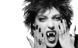 Female vampire screaming. Monochrome Beauty Fashion Portrait. Attractive female vampire with light colored evil eyes snarling at the camera in a gothic concept Stock Photo