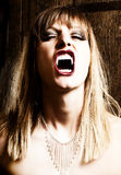 Female vampire showing her fangs. Blonde, female vampire with dangerous expression and open mouth is showing her fangs. Photo was taken in an old Viennese cellar Stock Photos