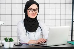Female veiled scientist sitting on her desk with fingers on a keyboard of her laptop, smiling stock photo