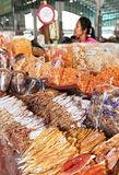 Female vendor selling a variety of salted dried fish stock photo