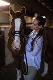Female vet examining brown horse. At stable Royalty Free Stock Photography
