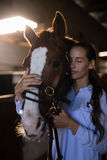 Female vet with eyes closed standing by horse at stable. Close up of female vet with eyes closed standing by horse at stable stock images