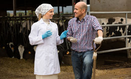 Female vet and farm worker in cowshed stock photo