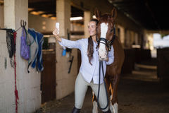 Female vet taking selfie with horse. In stable royalty free stock photo