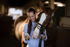 Female vet using mobile phone while standing by horse Stock Image
