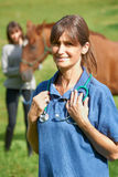 Female Vet Visiting Horse And Owner In Field Stock Images