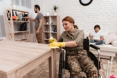 A female veteran in a wheelchair is cleaning the house. She`s in military uniform. Royalty Free Stock Photos