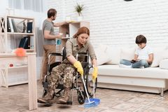 A female veteran in a wheelchair is cleaning the house. She`s in military uniform. Royalty Free Stock Image