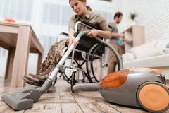 A female veteran in a wheelchair is cleaning the house. She`s in military uniform. Royalty Free Stock Photography