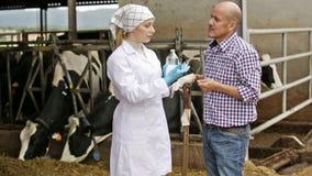 Female veterinarian talking to farm worker stock footage
