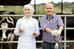 Female veterinarian talking to farm worker in cowshed. Attractive female veterinarian dressed in white coat holding glass with milk and talking to farm worker in Stock Image