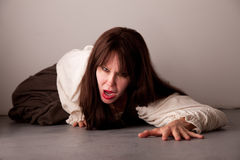 Female victim crawling on the floor Royalty Free Stock Photos