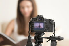 Female video blogger recording vlog on DSLR camera. Close up photo of camera on tripod with young woman reading book image on LCD back screen and blurred scene stock photos