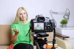 Female video blogger recording vlog or podcast, streaming online. Blurred camera on tripod in front. royalty free stock photos