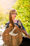 Female Viking Character. A beautiful female shield maiden viking character with fur and an ax in the foothills of a mountain. Fashion editorial influences stock photo