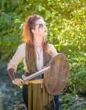 Female Viking Character. A beautiful female shield maiden viking character with fur and saex knife in the foothills of a mountain. Fashion editorial influences stock photography