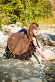 Female Viking Character. A beautiful female shield maiden viking character with fur and an ax in the foothills of a mountain. Model reaching into a creek royalty free stock image